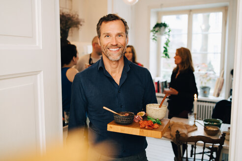 Portrait of smiling mature man holding food in serving tray while standing against friends at party - MASF09078