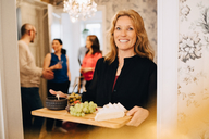 Portrait of smiling mature woman holding serving tray with friends standing in background - MASF09090