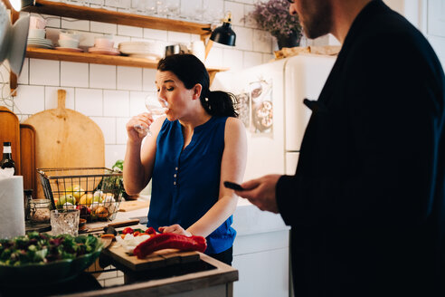 Male friend looking at mature woman drinking wine while standing in kitchen - MASF09093