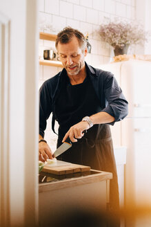 Mature man cutting cheese on board at kitchen counter - MASF09099