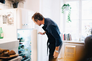 Mature man looking into refrigerator while standing at kitchen - MASF09105