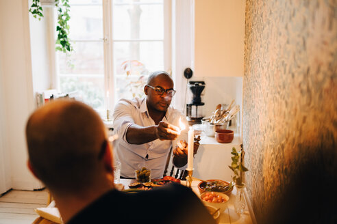 Man lighting candle while sitting with friend during dinner party at table - MASF09108