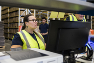 Confident mature female worker standing by coworker in distribution warehouse - MASF09117