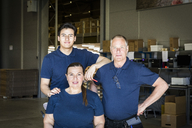 Portrait of confident multi-ethnic workers standing at distribution warehouse - MASF09123