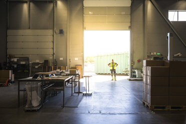 Full length of senior warehouse worker standing at storage room doorway - MASF09129
