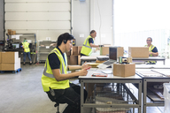 Young customer service representative talking through headset while coworkers at warehouse - MASF09132