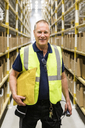 Portrait of smiling senior male worker holding package while standing on aisle at distribution warehouse - MASF09144