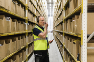 Senior male worker with digital tablet looking at packages on rack while talking through headset at distribution warehou - MASF09147