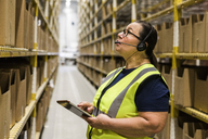 Mature female worker with digital tablet looking up while talking on headset at distribution warehouse - MASF09150