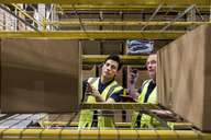 Male coworkers discussing over cardboard box while seen through rack at warehouse - MASF09153
