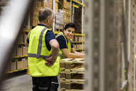 Smiling young worker looking at senior coworker standing at distribution warehouse - MASF09156