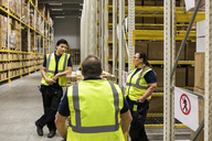 Multi-ethnic coworkers discussing while standing by racks at distribution warehouse - MASF09159