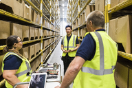 Multi-ethnic coworkers discussing while standing amidst racks at distribution warehouse - MASF09168