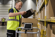 Side view of senior male worker packing merchandise in cardboard box on cart at distribution warehouse - MASF09177