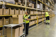 Full length of female worker pushing cart with cardboard boxes by rack against coworker at warehouse - MASF09180