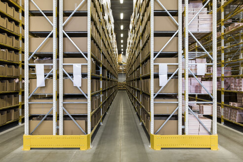 Empty narrow aisle amidst racks at distribution warehouse - MASF09183