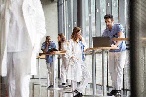 Young nurse discussing with mid adult doctor over laptop while standing against window at hospital - MASF09189