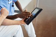 High angle view of male nurses discussing over digital tablet while sitting in corridor at hospital - MASF09201