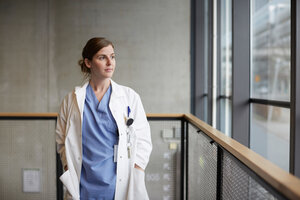Thoughtful female doctor standing with hands in pockets while looking through window at hospital corridor - MASF09213