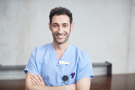 Portrait of smiling young male nurse in blue scrubs standing with arms crossed against wall at hospital - MASF09216