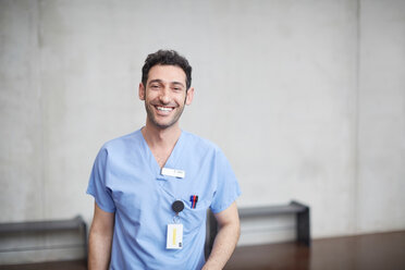Portrait of smiling young male nurse in blue scrubs standing against wall at hospital - MASF09219