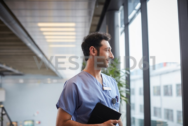 Thoughtful young male nurse holding digital tablet while looking through window at hospital - MASF09240