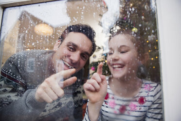 Father and daughter drawing in condensation on wet winter window - HOXF03773