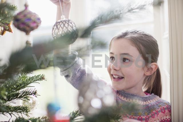 Girl decorating, hanging ornament on Christmas tree - HOXF03782 - Sam Edwards/Westend61
