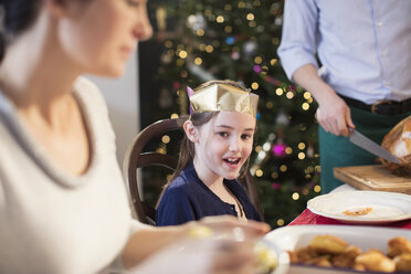 Smiling girl wearing paper crown at Christmas dinner - HOXF03797