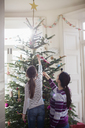 Mother and daughter decorating Christmas tree - HOXF03809
