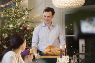 Man serving Christmas turkey to family at candlelight dinner table - HOXF03812