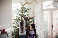Mother and daughter decorating Christmas tree - HOXF03839