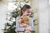 Happy girl hugging teddy bear in front of Christmas tree - HOXF03848