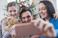 Happy family with smart phone taking selfie in Christmas living room - HOXF03860