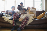 Young family relaxing in pajamas on living room sofa - HOXF03890
