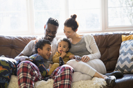 Multi-ethnic young family relaxing in pajamas on living room sofa - HOXF03896