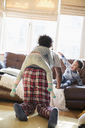 Father and kids in pajamas playing in living room - HOXF03899