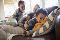 Portrait happy mother and children cuddling on living room sofa - HOXF03938
