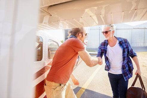 Pilot shaking hands with man boarding small airplane - CAIF21745