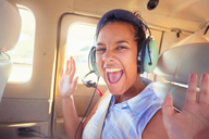 Portrait enthusiastic young woman with headphones riding in airplane - CAIF21760