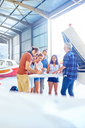 Friends planning trip at map in airplane hangar - CAIF21763