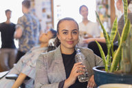 Portrait confident businesswoman drinking bottled water in office - CAIF21823