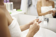 Woman using dental floss in bathroom, partial view - ABIF00988