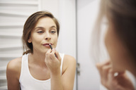 Mirror image of young woman in bathroom applying lipliner - ABIF01000