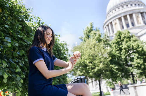 UK, London, young woman using her smartwatch near St. Paul's Cathedral - MGOF03777