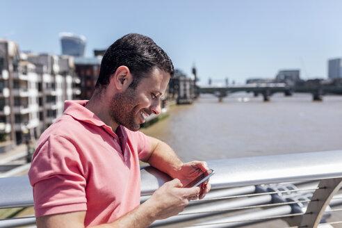UK, London, man using his smartphone on the Millennium Bridge - MGOF03783