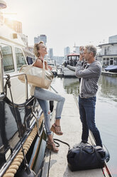 Older man taking picture of young woman on jetty next to yacht - RORF01551