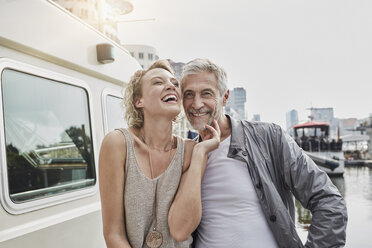 Happy older man and young woman on jetty next to yacht - RORF01554