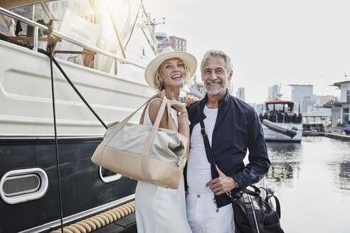 Older man and young woman standing with travelling bags on jetty next to yacht - RORF01557