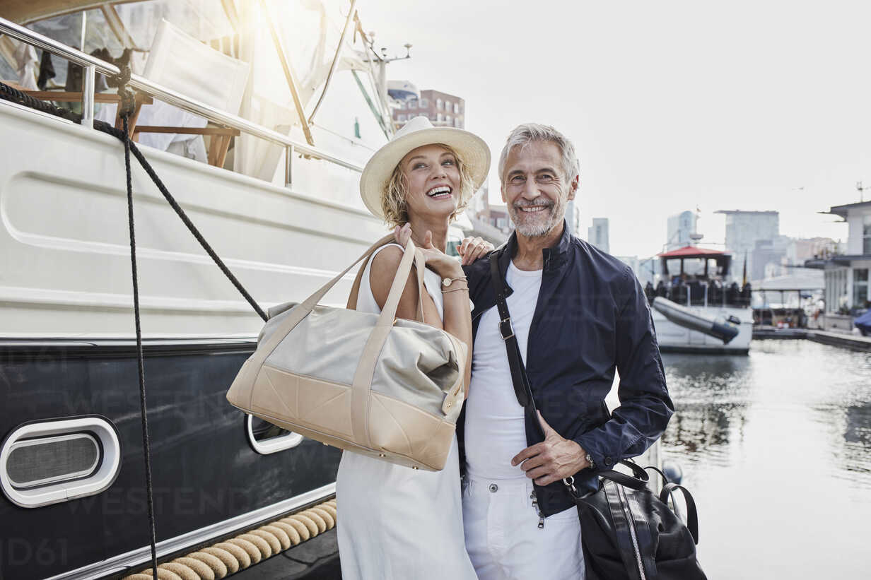 Older man and young woman standing with travelling bags on jetty next to yacht - RORF01557 - Roger Richter/Westend61